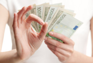 the girl holding a money and showing her hand with okay sign